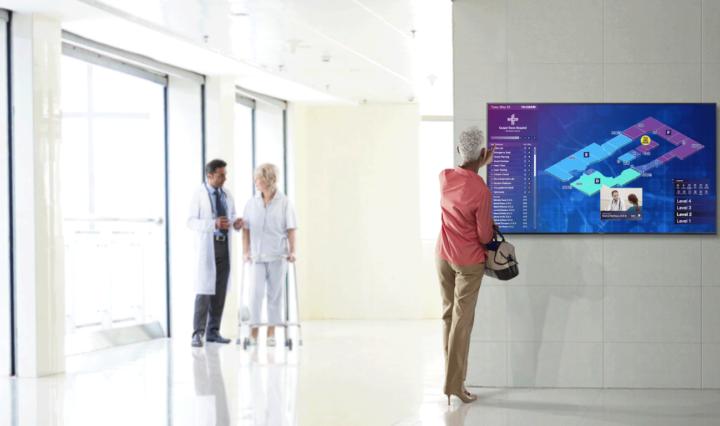 Woman uses digital signage to navigate a hospital.