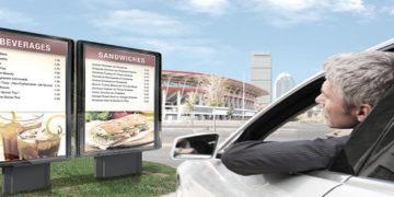 A man in car looking at outdoor digital menu board