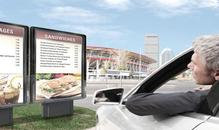A man in car looking at outdoor digital menu board